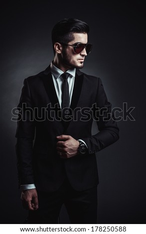 Portrait of handsome stylish man in elegant black suit and sunglasses - stock photo