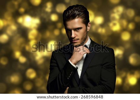 Portrait of handsome stylish man in elegant black suit golden bokeh - stock photo