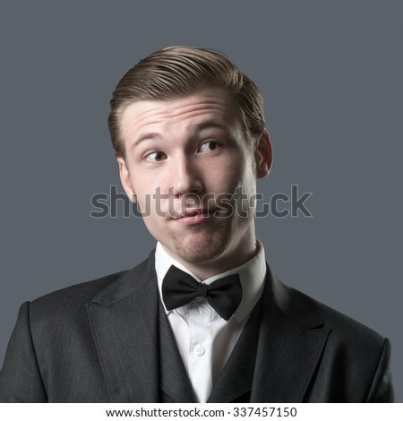 Portrait of handsome stylish man in elegant black suit, isolated on gray - stock photo