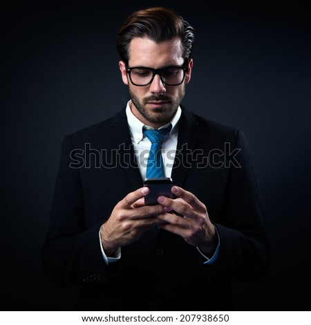 Portrait of handsome stylish man in elegant black suit using mobile phone. Isolated on black. - stock photo