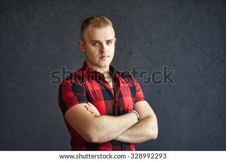 Portrait of handsome stylish man in plaid shirt on grey textured background