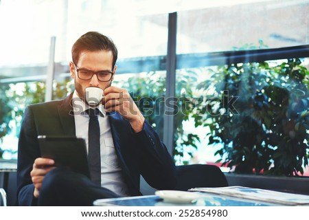 Portrait of handsome successful man drink coffee and look to the digital tablet screen sitting in coffee shop, business man having breakfast sitting on beautiful terrace with plants - stock photo