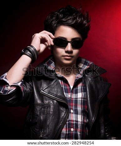 Portrait of handsome teen boy wearing stylish sunglasses and leather jacket over dark red background, teenage fashion and style