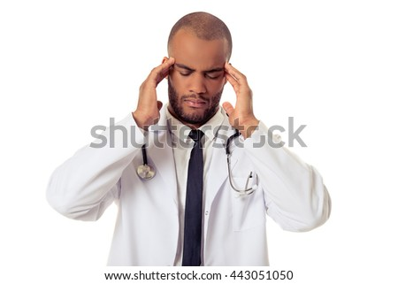 Portrait of handsome tired Afro American doctor in white coat massaging his temples, isolated on white background
