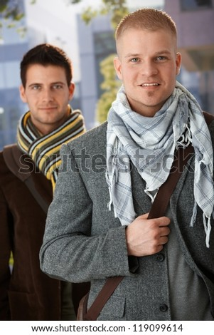 Portrait of handsome trendy men wearing scarf, standing outside, smiling at camera. - stock photo