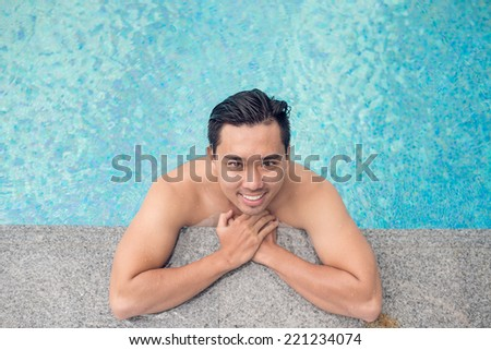 Portrait of handsome Vietnamese man relaxing in the swimming pool, view from above - stock photo