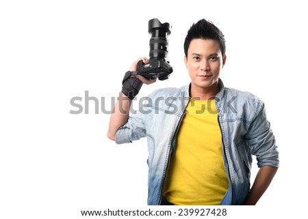 Portrait of handsome Vietnamese photographer holding a digital camera - stock photo