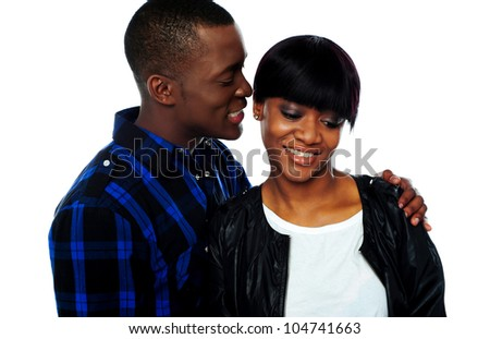 Portrait of handsome young african man whispering in his girlfriends ear