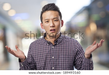 portrait of handsome young asian man doubting - stock photo