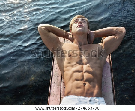 Portrait of handsome young athletic man lying on wooden small jetty against sea water background - stock photo