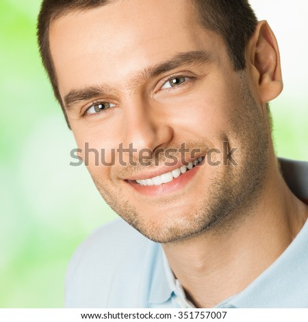 Portrait of handsome young attractive smiling man, outdoor