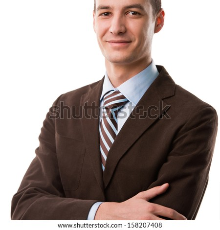 Portrait of handsome young business man standing with hands folded and smiling on white background - stock photo