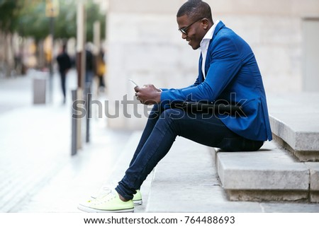 Portrait of handsome young business man using his mobile phone in the street.