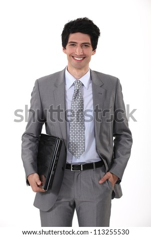 portrait of handsome young businessman all smiles with laptop - stock photo