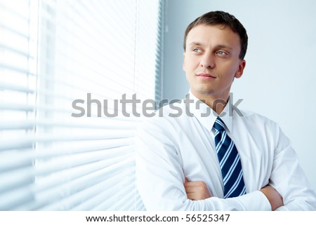 Portrait of handsome young businessman by the window - stock photo