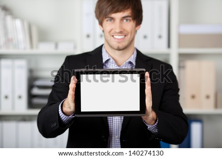 Portrait of handsome young businessman displaying digital tablet in office - stock photo