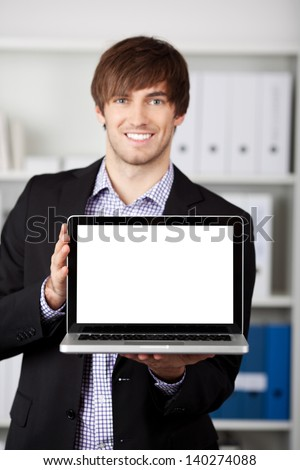 Portrait of handsome young businessman displaying laptop t in office - stock photo