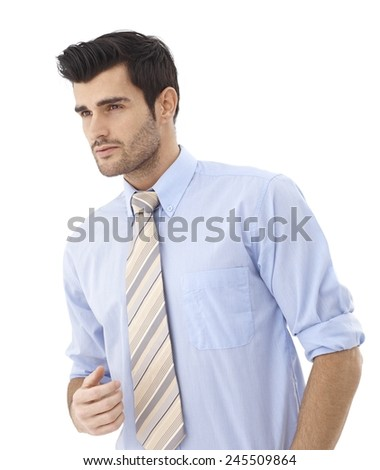 Portrait of handsome young businessman in shirt and tie looking away. - stock photo