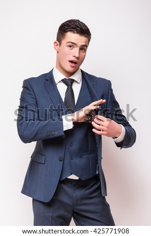 Portrait of Handsome young businessman  in suit standing against white background - stock photo