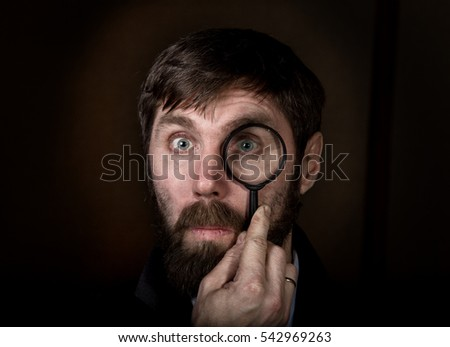 portrait of handsome young businessman looking through magnifying glass on a brown background