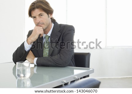 Portrait of handsome young businessman sitting at conference table