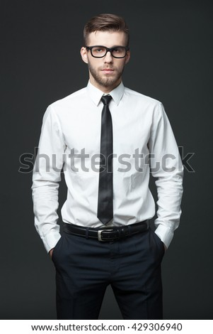 Portrait of handsome young businessman standing against dark gray background. - stock photo