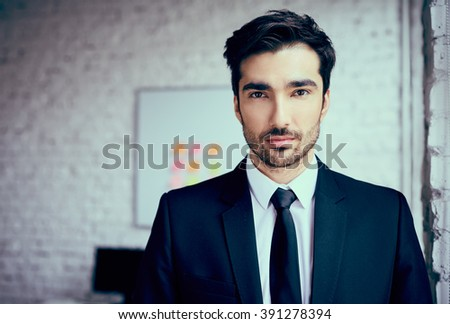 Portrait of handsome young businessman standing in office - stock photo
