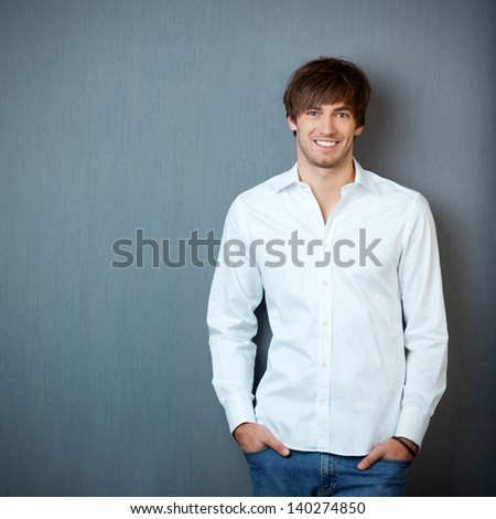 Portrait of handsome young businessman standing with hands in pockets against blue wall - stock photo