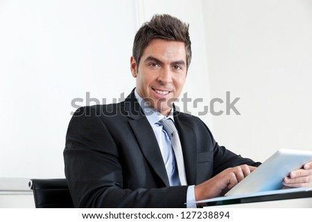 Portrait of handsome young businessman using digital tablet in office - stock photo