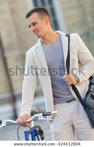 Portrait of handsome young businessman walking on the city street with his bicycle beside him - stock photo