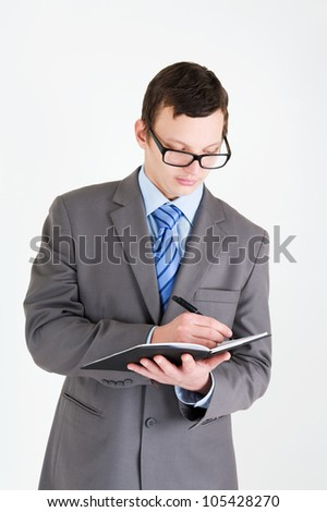 Portrait of handsome young businessman with notebook\ - stock photo