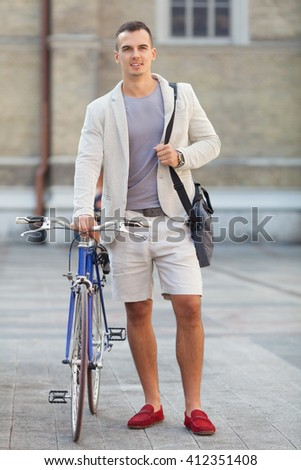 Portrait of handsome young businessmant with his bicycle beside him. - stock photo