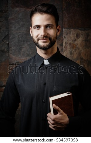 Portrait of handsome young catholic priest with prayer book against dark background.