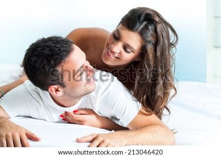 Portrait of handsome Young couple sharing intimacy in bedroom. - stock photo