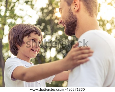Portrait of handsome young dad and his cute little son looking at each other and smiling while resting in park - stock photo