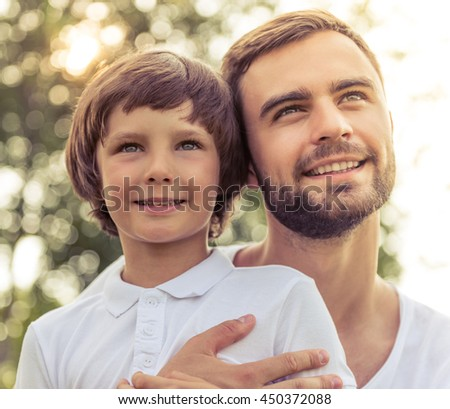 Portrait of handsome young dad and his cute little son looking forward and smiling while resting outdoors - stock photo