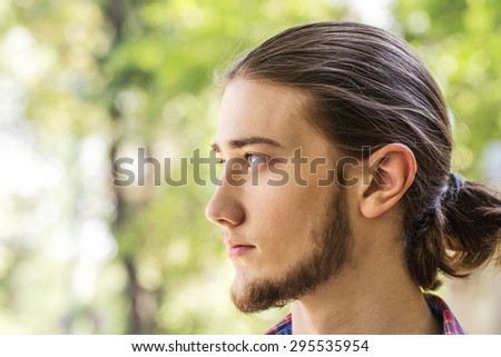 Portrait of handsome young long hair and bearded brunette man at outdoors. Side view. Photo taked against park trees. - stock photo