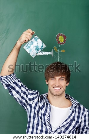 Portrait of handsome young male student holding watering can with flower drawn on chalkboard representing growth of ideas - stock photo