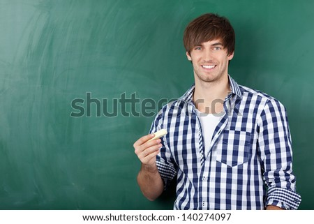 Portrait of handsome young male student in front of chalkboard