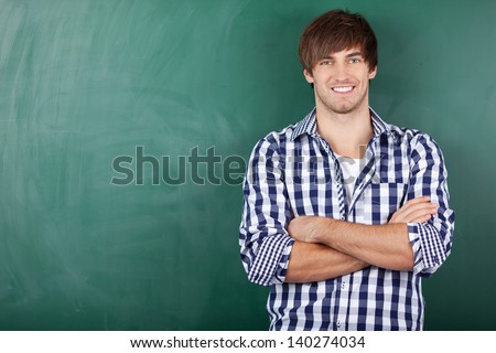 Portrait of handsome young male student with arms crossed standing against chalkboard