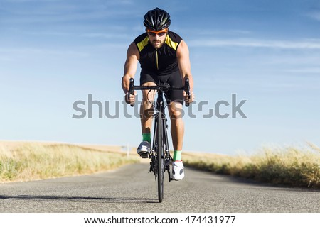 Portrait of handsome young man cycling on the road.
