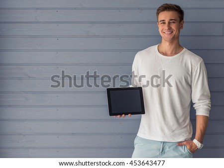 Portrait of handsome young man in casual clothes holding a digital tablet, looking at camera and smiling, standing against gray wall