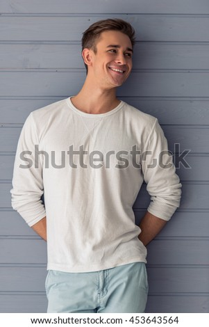 Portrait of handsome young man in casual clothes looking away and smiling, standing against gray wall