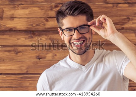 Portrait of handsome young man in eyeglasses looking at camera and smiling, against wooden wall - stock photo