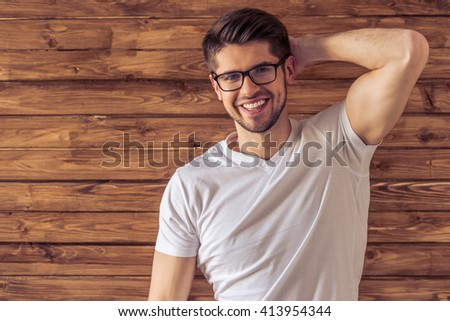 Portrait of handsome young man in eyeglasses looking at camera and smiling, standing against wooden wall