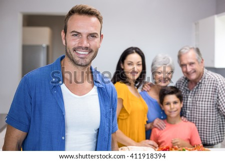 Portrait of handsome young man in the kitchen and other family member standing in background - stock photo