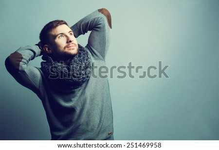 portrait of handsome young man in trendy casual sweater and scarf. - stock photo