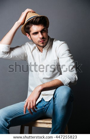 Portrait of handsome young man in white shirt, jeans and hat over grey background