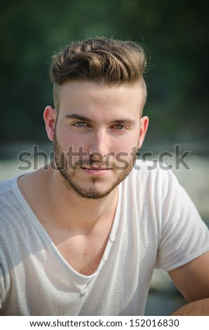 Portrait of handsome young man in white t-shirt outdoors, looking in camera - stock photo