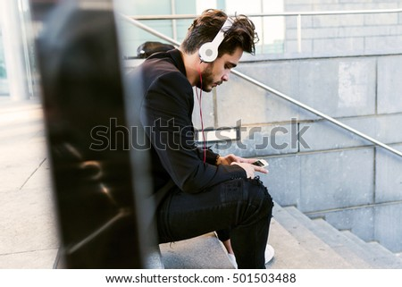Portrait of handsome young man listening to music with mobile phone in the street.